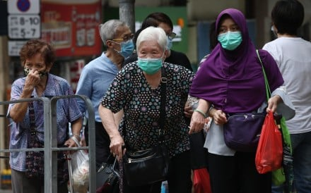 A domestic helper crosses the road with an elderly woman. Photo: SCMP / Jonathan Wong