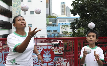 Anik Herawati Liechti and son Max, 8, juggle balls at Po Leung Kuk Lam Man Chan English Primary School in To Kwa Wan. They are part of a pilot project aimed at getting kids to be more physically active. Photo: Xiaomei Chen