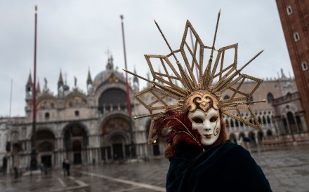 A Venetian wearing a carnival mask and costume at St Mark's square in Venice on Sunday. Photo: AFP