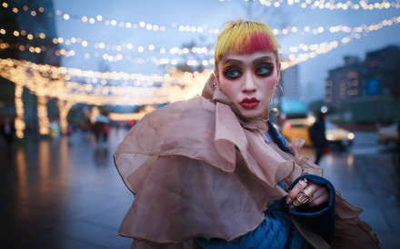 With hair dyed a striking yellow with blotches of orange and hot pink and eyes painted tangerine and crimson, Taiwanese glam rocker Wednesday Wu seems comfortable in her own skin.