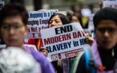 An activist from the Asian Migrants Coordinating Body holds a placard that reads 'End Modern Day Slavery in HK' during a protest on March 8. Photo: AFP