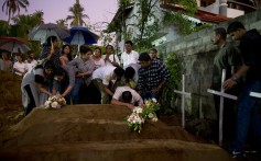 Relatives place flowers after the burial of three victims of the same family, who died at Easter Sunday bomb blast at St. Sebastian Church in Negombo, Sri Lanka. Photo: AP