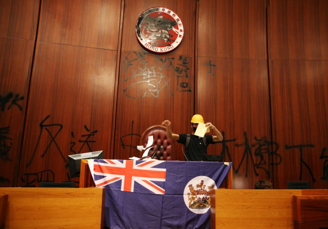 A protester is tearing apart a copy of the Basic Law in the Legislative Council chamber on Monday.