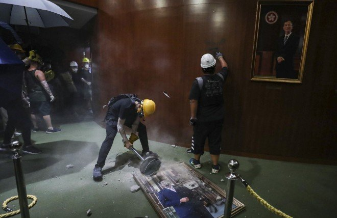 A protester is smashing the portrait of Legislative Council President Andrew Leung.
