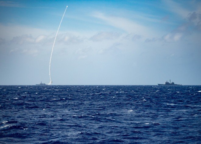 The guided-missile destroyer USS Barry (left) launches a missile during a live-fire exercise on Thursday.