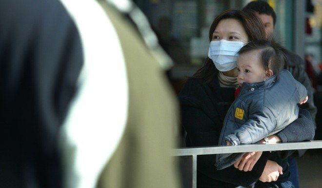 A woman travels with a baby during the Sars outbreak in December 2003.