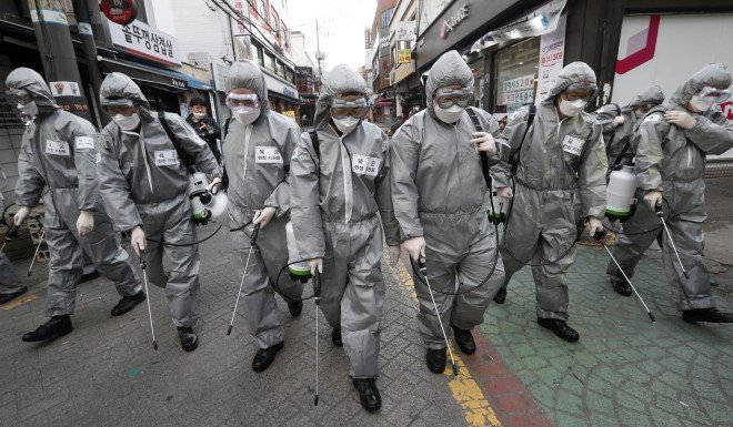South Korean soldiers spray disinfectant at a shopping street in Seoul.