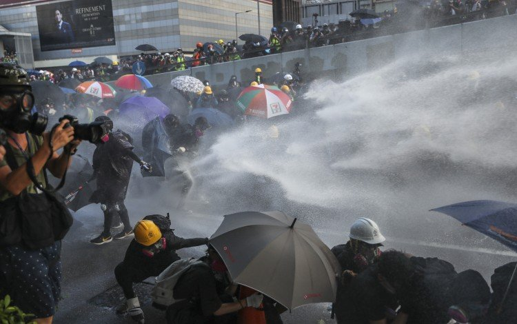 Riot police fire water cannon at demonstrators in Hong Kong earlier this month. Anti-government protests have gripped the city since early June. Photo: Sam Tsang