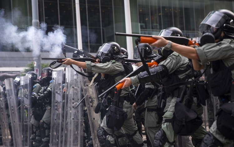 Riot police fire non-lethal rounds to disperse protesters in the Admiralty district of Hong Kong on Sunday. The violence escalated on Tuesday when an officer shot a protester at close range in the chest with a live round. Photo: Bloomberg
