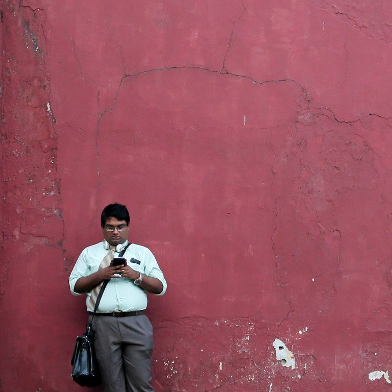 A man in Colombo, Sri Lanka, uses his mobile phone. Beijing is actively exporting its internet successes, empowering businesses to transact online through the same tools developed in China. Photo: Reuters