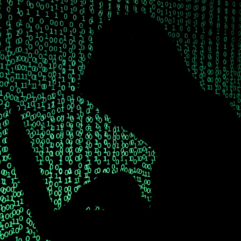 A hooded man holds a laptop computer as cyber code is projected on him in this illustration picture. Photo: Reuters