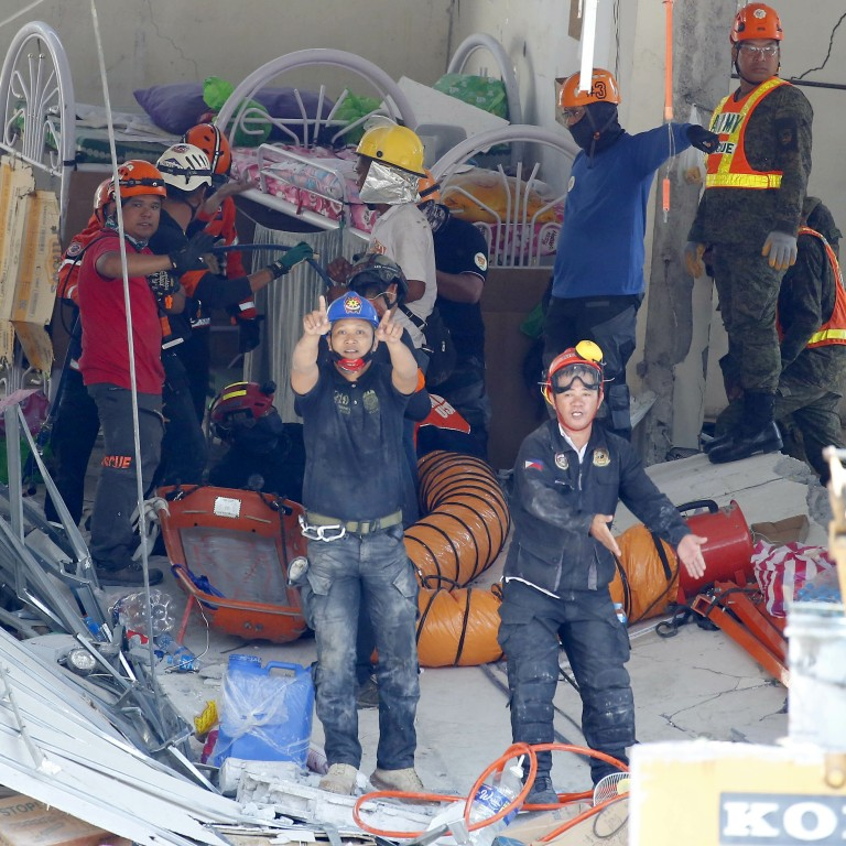 46ea77efa29b0 Rescuers gesture to clear the way following the discovery of a survivor in  a collapsed commercial