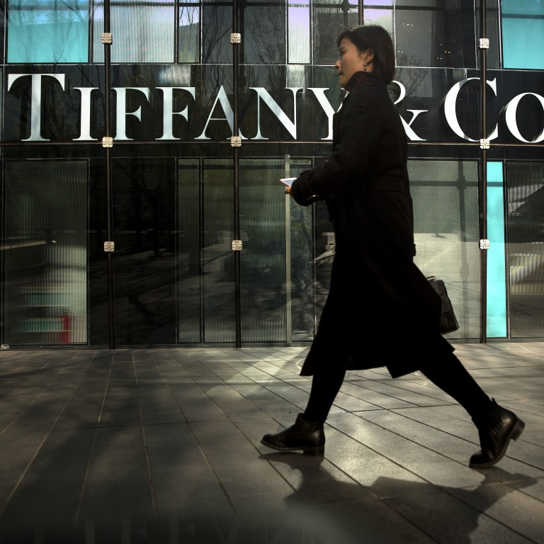 686d5c3d9 A woman walks past a Tiffany & Co. store in Beijing in November. Photo