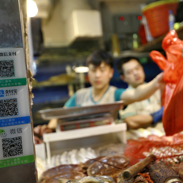 Cashless payment platforms through smartphone-enabled QR codes are ubiquitous in China, expanding to a US$12.8 trillion market by the end of October in 2017. Ant Financial's Alipay and Tencent's WeChat Pay are the two dominant service providers. Here a seafood hawker in Beijing announces he accepts both payment methods. Photo: EPA