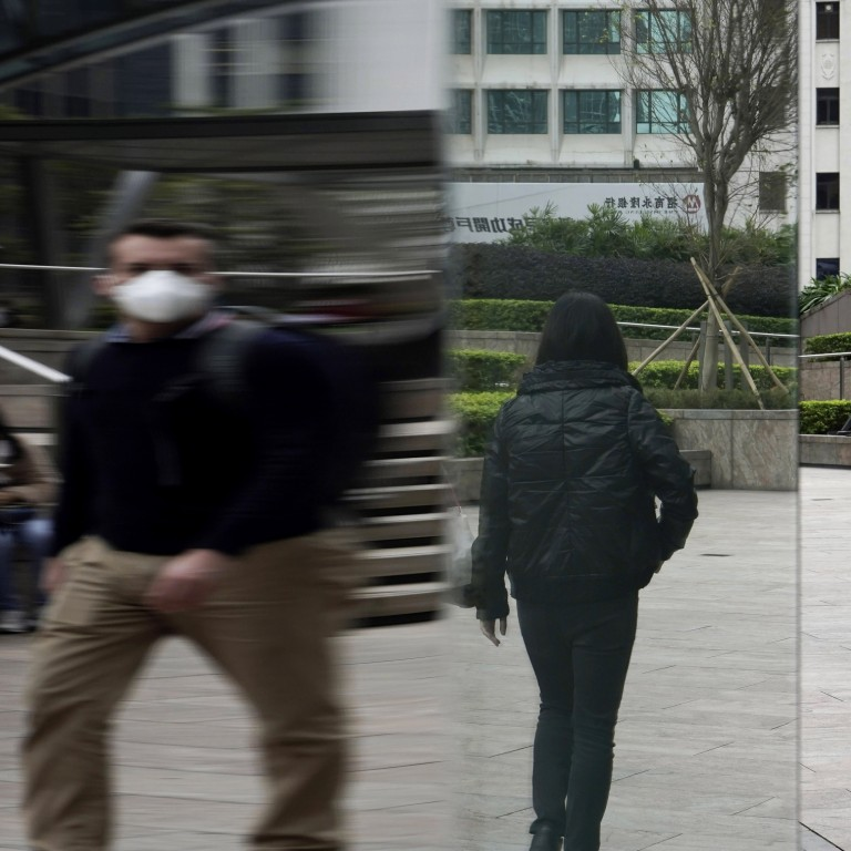 People wearing protective face masks, walk on a street in Central, Hong Kong. A KPMG survey found demand for tech talent is expected to increase among companies as businesses adapt to new economic realities due to the coronavirus pandemic. Photo: AP Photo