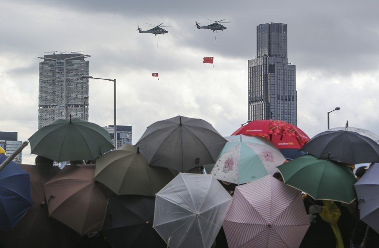 Hong Kong officials will watch China's flag rise indoors to avoid clashes