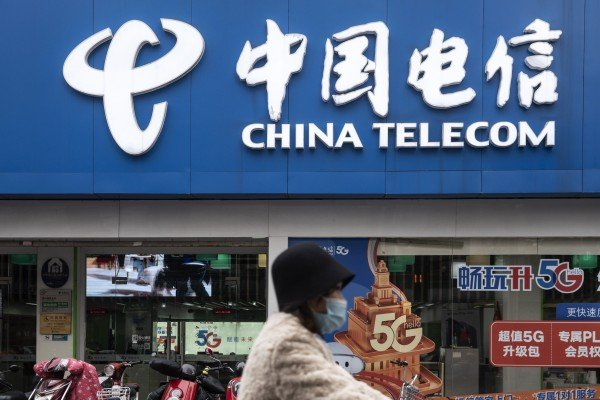 A motorist wearing a protective mask goes past a China Telecom store in Shanghai. Photo: Bloomberg