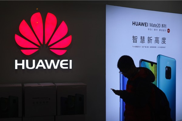 A man browses his smartphone outside a Huawei store at a shopping mall in Beijing. Photo: AP