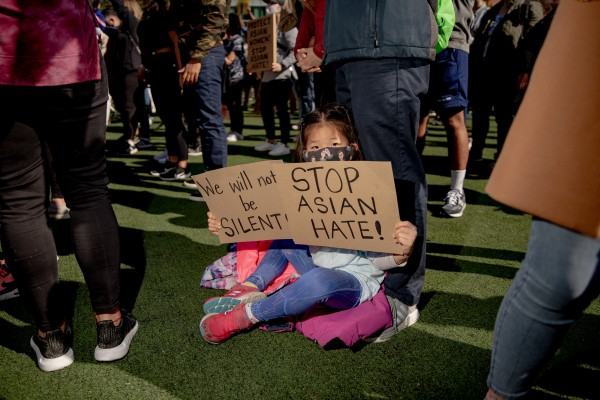 A child holds signs during an AAPI Rally Against Hate in New York on March 21. Photo: Bloomberg