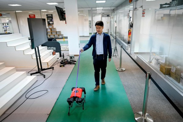 Ma Jie, chief technology officer for Weilan, walks an AlphaDog at the company workshop in Nanjing. Photo: AFP