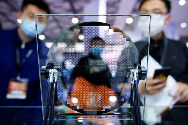 Visitors look at a display of a semiconductor device at Semicon China, a trade fair for semiconductor technology, in Shanghai, China March 17, 2021. REUTERS/Aly Song