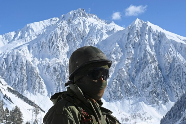 An Indian army soldier stands on a snow covered road in the Himalayas. Photo: AFP