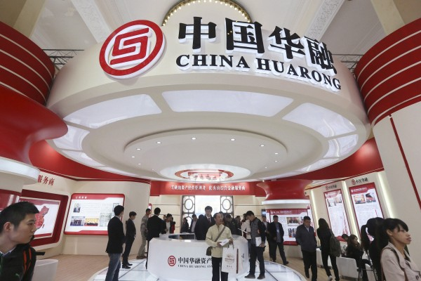China Huarong Asset Management Company both at a finance expo in Beijing in 2014. The company's dollar-denominated bonds have declined sharply in recent weeks after it missed a deadline to report its annual results in March. Photo: Reuters