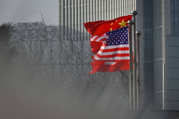 Chinese and US national flags flutter at the entrance of a company office building in Beijing. Photo: AFP