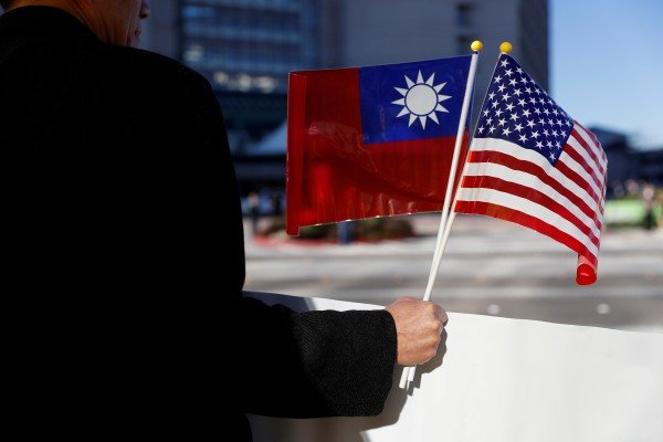 A man holds flags of Taiwan and the United States. Photo: Reuters