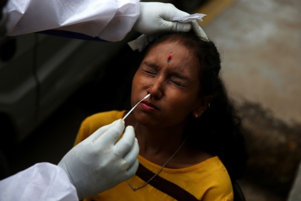 An Indian health worker collects a nasal swab sample from a woman in Bangalore. Photo: EPA
