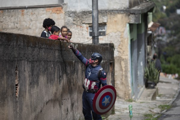 Military police officer Everaldo Pinto, dressed as Captain America, advises children on the need to protect themselves against Covid-19, in Petropolis, Rio de Janeiro state, Brazil. Photo: AP
