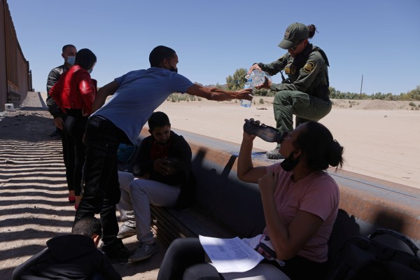 A US Border Patrol officer gives water to detained migrants  in Andrade, California who crossed into the United States from Mexico on Monday. Photo: Reuters