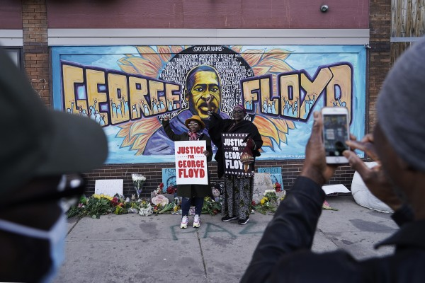 People pose for pictures in front of a mural for George Floyd in Minneapolis. Photo: AP