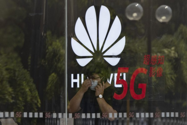 A worker wearing a mask speaks on the phone near the Huawei logo in a store in Beijing. Photo: AP