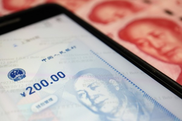 China's official app for digital yuan is seen on a mobile phone next to 100-yuan banknotes. Photo: Reuters