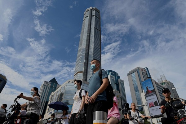 People walk past the temporarily closed 300-meter (1,000-ft.) SEG Plaza (C) in the southern Chinese city of Shenzhen in Guangdong province on May 24, 2021. Photo: AFP