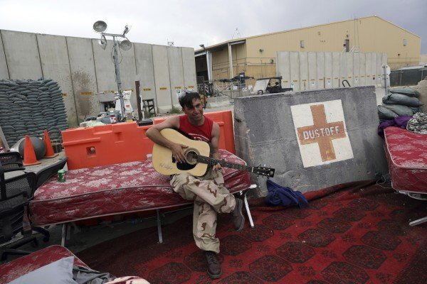 An Afghan soldier plays a guitar that was left behind after the American military departed Bagram air base in Afghanistan on July 5. Photo: AP