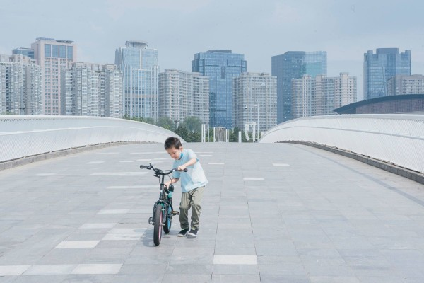 A boy pushes his bike along the bridge that connects the Hongbaihua Park and Ruyi Lake Cultural Square in Zhengzhou, China, in August. Photo: Bloomberg Businessweek / Yufan Lu
