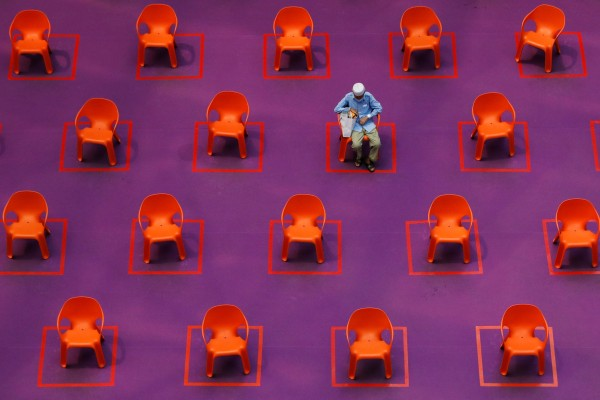 A man sits among empty seats at a free movie screening in Singapore, on September 29, as restrictions on social gathering are tightened due to the surge of Covid-19 cases. Photo: Reuters