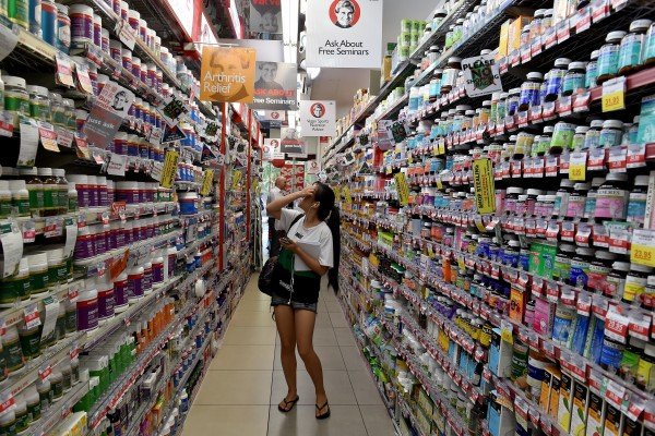 A shopper browsing through shelves of health supplements in a supermarket in Sydney. Photo: AFP