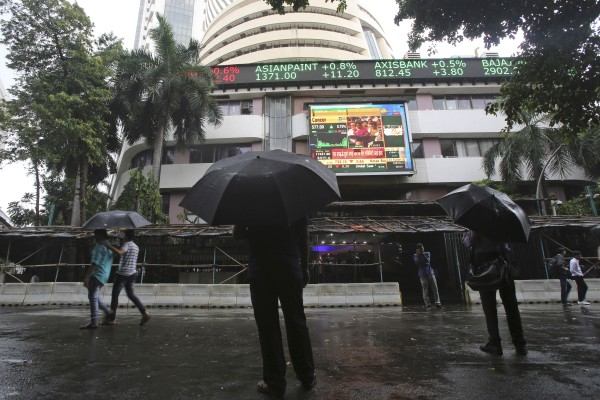 Passersby watch the stock market index on a display screen in Mumbai. Authorities are investigating a series of recent suspected cyber intrusions which could have led to a power outage in the city, crippled systems at banks and caused a glitch at a key stock exchange. Photo: AP