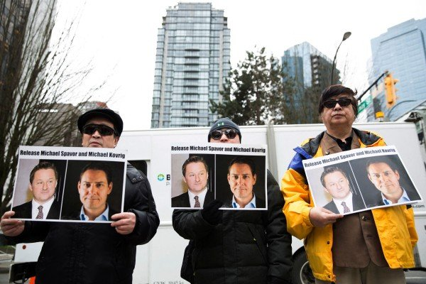 Protesters hold photos of Canadians Michael Spavor and Michael Kovrig, who are being detained by China, outside the British Columbia Supreme Court in Vancouver in March 2019. Photo: AFP