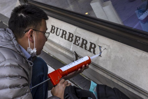 A damaged logo on the front of the Burberry store in Shanghai is repaired on Friday. Burberry is one of the international brands suffering a Chinese backlash over Xingjiang. Photo: EPA-EFE