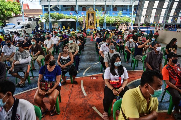 People wait to receive Covid-19 vaccinations at a school in Bangkok. Photo: AFP