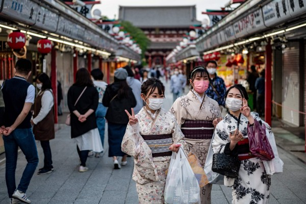 Women in traditional outfits and face masks visit Sensoji temple in Tokyo. Photo: AFP