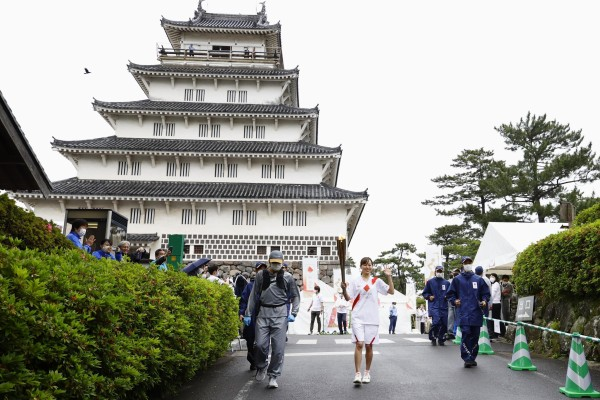 A Tokyo Olympic torch relay participant runs from Shimabara Castle in the Nagasaki prefecture city of Shimabara on Friday. Photo: Kyodo