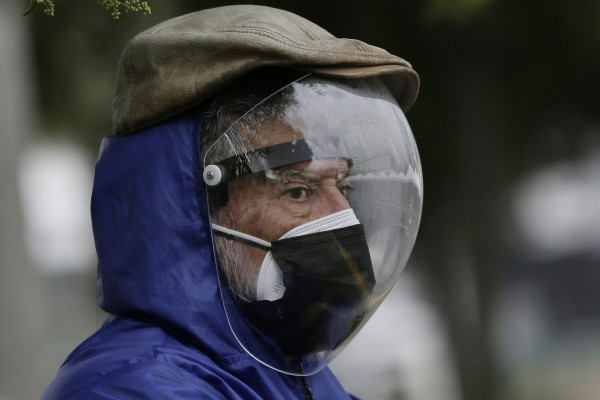 A man wearing a full protective face shield and double mask waits to be vaccinated in Quito, Ecuador. Photo: AP