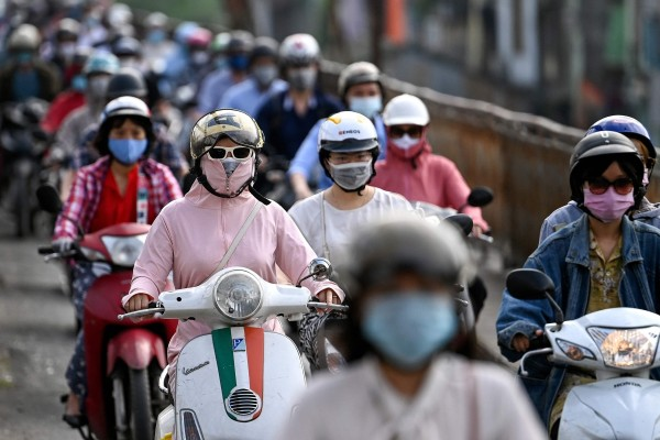 Morning commuters wearing face masks, amid concerns over Covid-19, in Hanoi. Photo: AFP