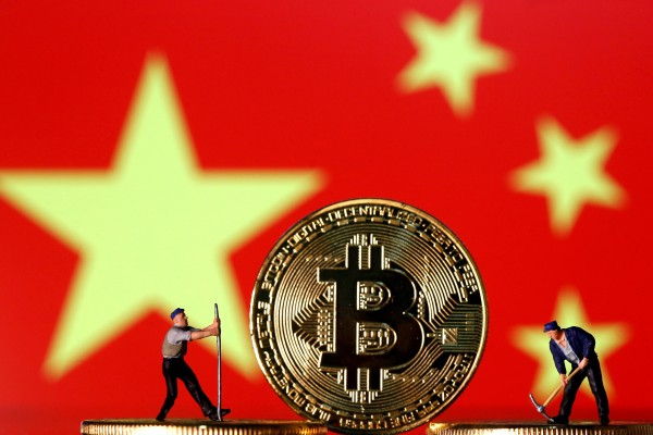 Small toy figurines are seen on representations of the Bitcoin virtual currency displayed in front of an image of China's flag. Photo: Reuters