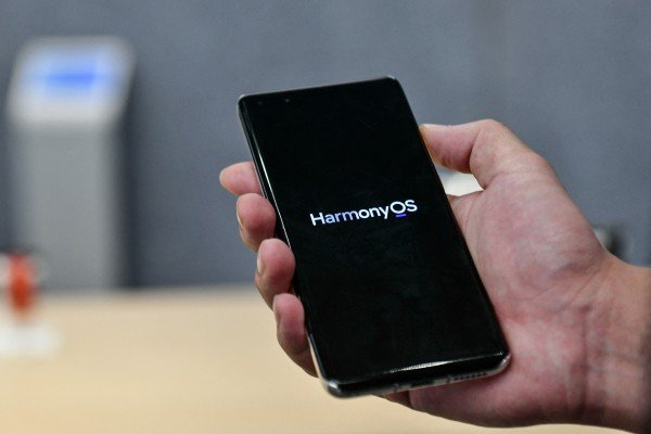 A staff member displaying a Huawei smartphone with the HarmonyOS operating system at the Huawei flagship store in Shenzhen, in China's southern Guangdong province, on May 31, 2021. HarmonyOS 2 is the company's effort to bridge the gap between smartphones, tablets and myriad IoT devices has it tries to move away from Android. Photo: AFP
